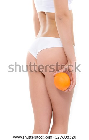Young woman in underwear with orange and perfect body showing absence of cellulite over white background