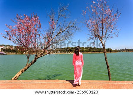 Young woman in Vietnamese traditional long dress (Ao dai) by Ho Xuan Huong Lake, Da Lat Provine, Viet Nam