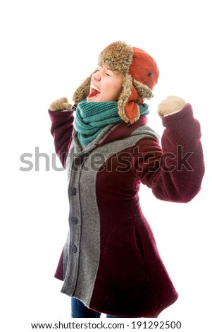 Young woman in warm clothing and celebrating success - stock photo