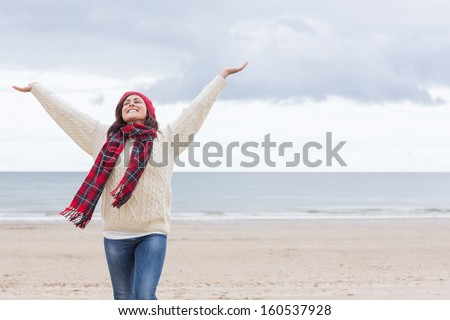 Young woman in warm clothing stretching her arms on the beach - stock photo