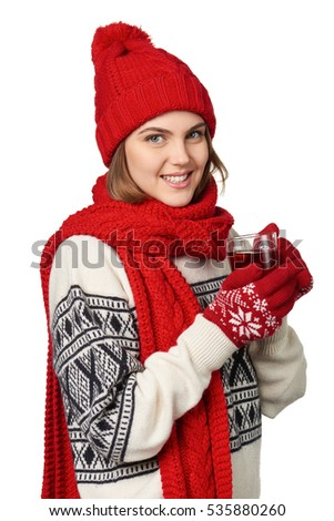 Young woman in warm winter clothing with cup of tea on white background