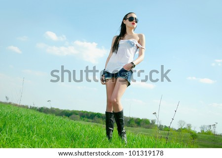 Young woman in wet t-shirt standing in a field