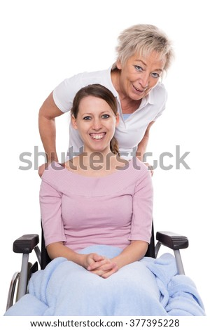 young woman in wheelchair, aged nurse behind her, isolated on white