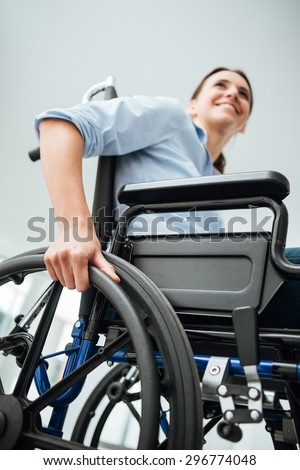 Young woman in wheelchair smiling and looking away, disability concept - stock photo
