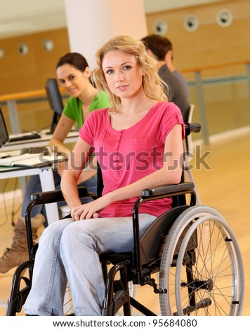 Young woman in wheelchair working in office - stock photo