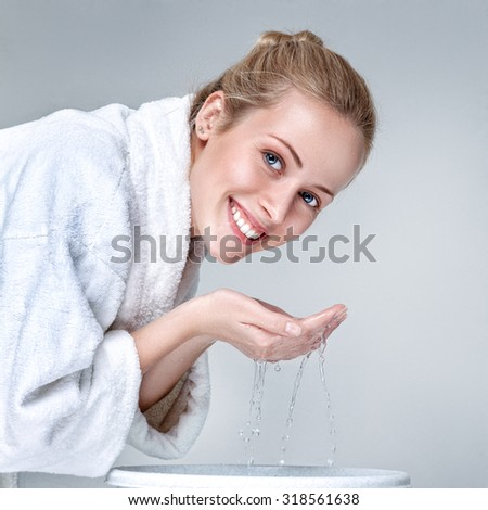 Young woman in white bathrobe washing face with clean water at morning - stock photo