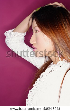 Young woman in white blouse, hand on head, profile