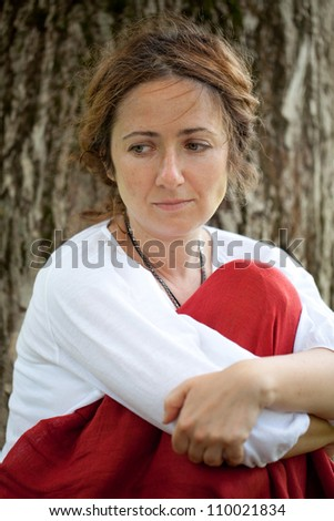 Young woman in white blouse with a sad face - stock photo