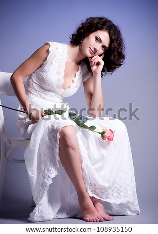 Young woman in white bridal dress with flowers