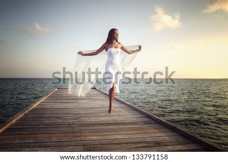 Young woman in white clothes posing on a pier on Maldives - stock photo