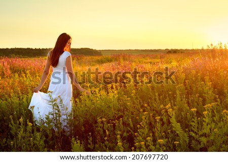 Young woman in white clothes standing in field on sunset - stock photo