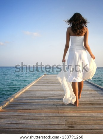 Young woman in white clothes walking on a pier on Maldives - stock photo