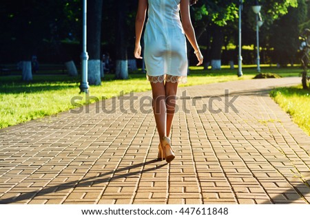 Young woman in white dress and high heels shoes walking down the avenue in the park