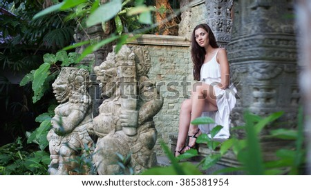 Young woman in white dress is sitting on the stairs of ancient buddhist temple.