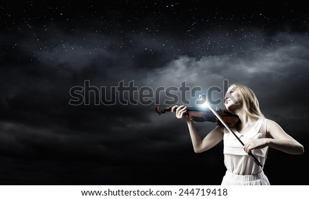 Young woman in white dress playing violin - stock photo