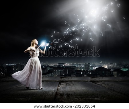 Young woman in white dress playing violin at night - stock photo
