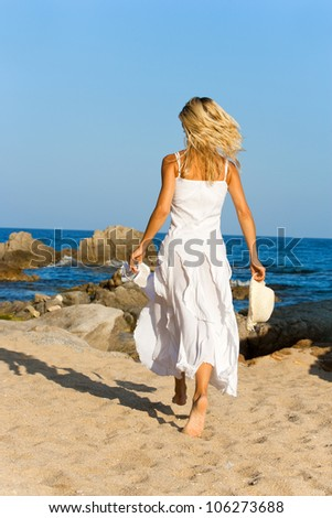 Young woman in white dress running on beach. - stock photo