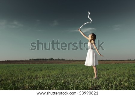 Young woman in white dress with white ribbon standing on grass over dark sky background