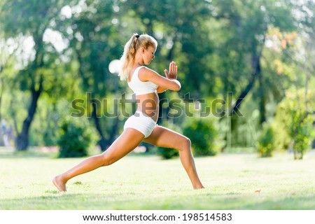 Young woman in white in summer park practicing yoga
