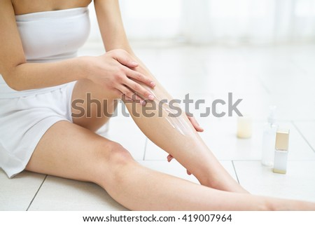 Young woman in white is engaged in the body care - stock photo