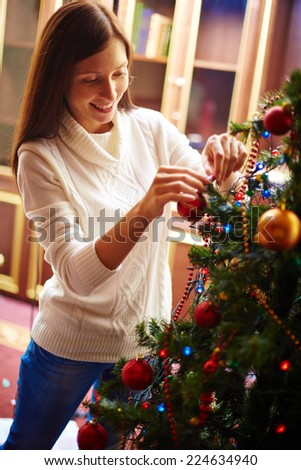 Young woman in white knitted sweater decorating Christmas tree - stock photo