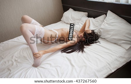 Young woman in white lingerie posing on bed. Sexy naked brunette. Sexy Lady on white bed. with censored. - stock photo