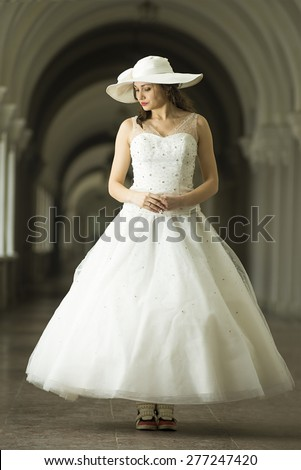 Young woman in white long dress and hat in sneakers. Long Shot. LS - stock photo