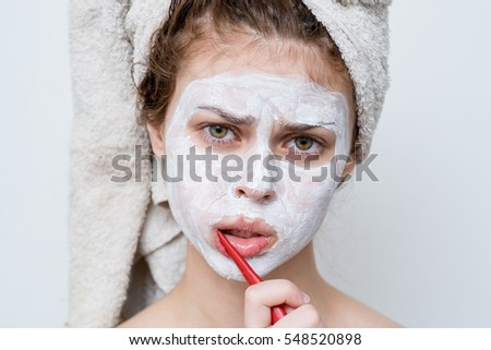 Young woman in white mask cosmetic brushes his teeth with a sour face at the camera