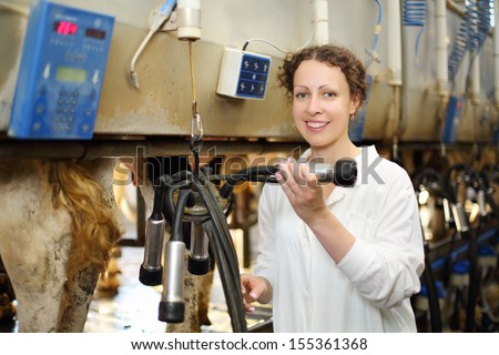 Young woman in white robe shows machine for milking of cows in big farm. - stock photo