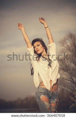 young woman in white shirt and jeans with arms up stand in wind, natural light, outdoor summer day - stock photo