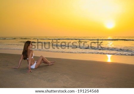 Young woman in white swimwear sitting on the sunset beach  - stock photo