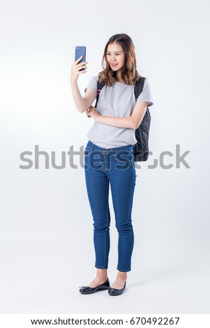 young woman in white t-shirt and blue jeans useing mobile phone