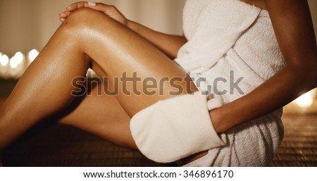 Young woman in white towel massaging his leg with white glove