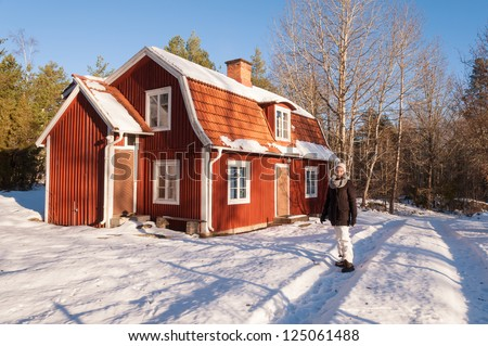 Young woman in winter clothes in front of a characteristic red wooden house in Sweden in a wonderful winter landscape - stock photo