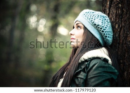 young woman in winter clothes outdoor portrait by tree profile - stock photo