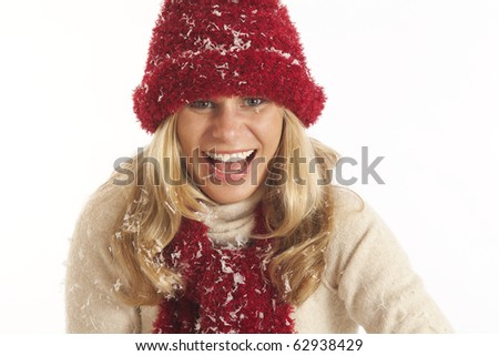 Young woman in winter clothes playing with snow