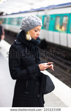 Young woman in winter coat with a cell phone in her hand waiting on the platform of a railway station for train to arrive. Public transport.   - stock photo