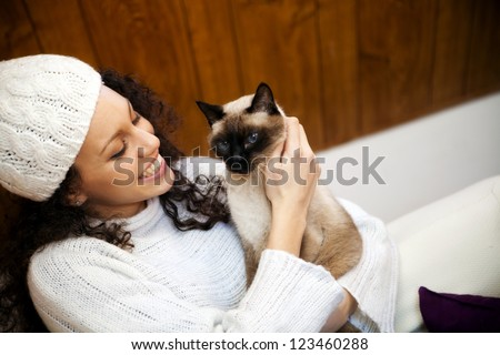 Young woman in winter in a cozy attic with her cat - stock photo