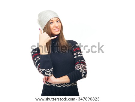 Young woman in winter sweater showing hand sign phone. Beautiful girl on a white background. Woman is symbolic shows that you need to call. Make a call to the pay phone concept for advertising.