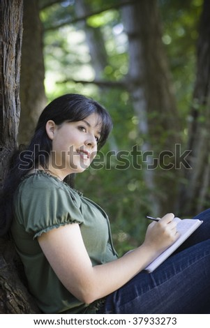 Young Woman In Woods Writing in Journal Looking Away from Camera