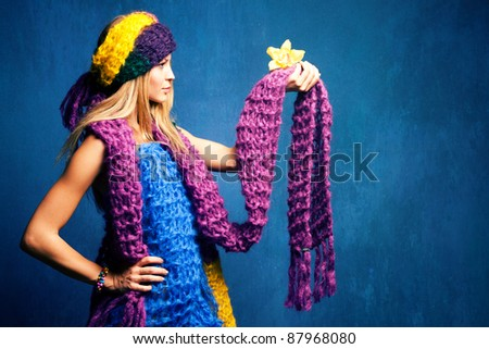 young woman in wool scarfs and flower in hand, studio shot - stock photo