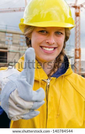 Young woman in work wear with thumb up - stock photo