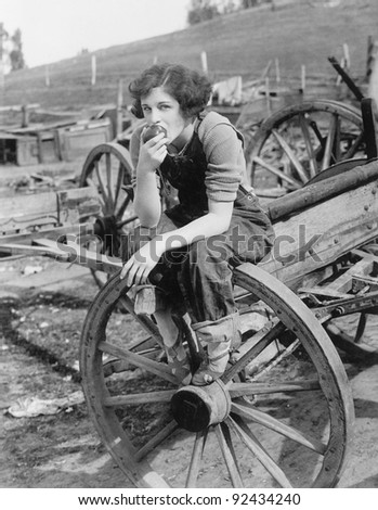 Young woman in working jeans sitting on wheel eating an apple - stock photo