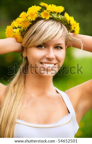 Young woman in wreath from yellow dandelions.