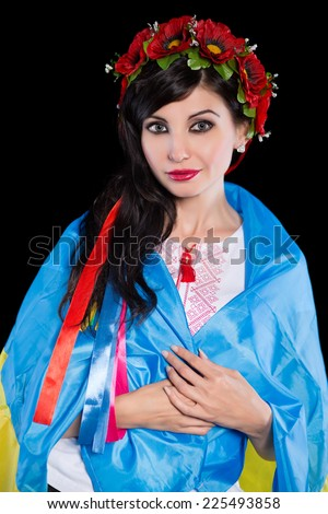 Young woman in wreath wrapped in Ukrainian flag. Isolated on black