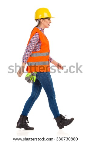 Young woman in yellow hardhat, orange reflective vest, lumberjack shirt, jeans, black boots,walking and looking away. Side view. Full length studio shot isolated on white.