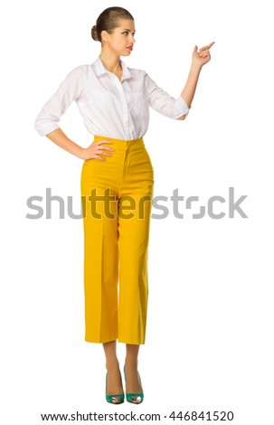 Young woman in yellow pants shows pointing gesture - stock photo