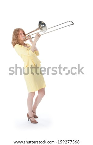 young woman in yellow playing trombone and white background - stock photo