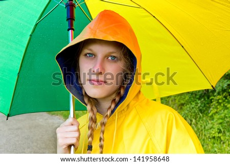 Young woman in yellow raincoat holding a umbrella - stock photo
