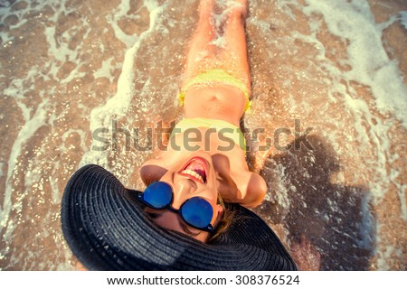 Young woman in yellow swimsuit with big hat and sunglasses engoying sun and water lying on the sandy beach. Photo with cross processing filter - stock photo